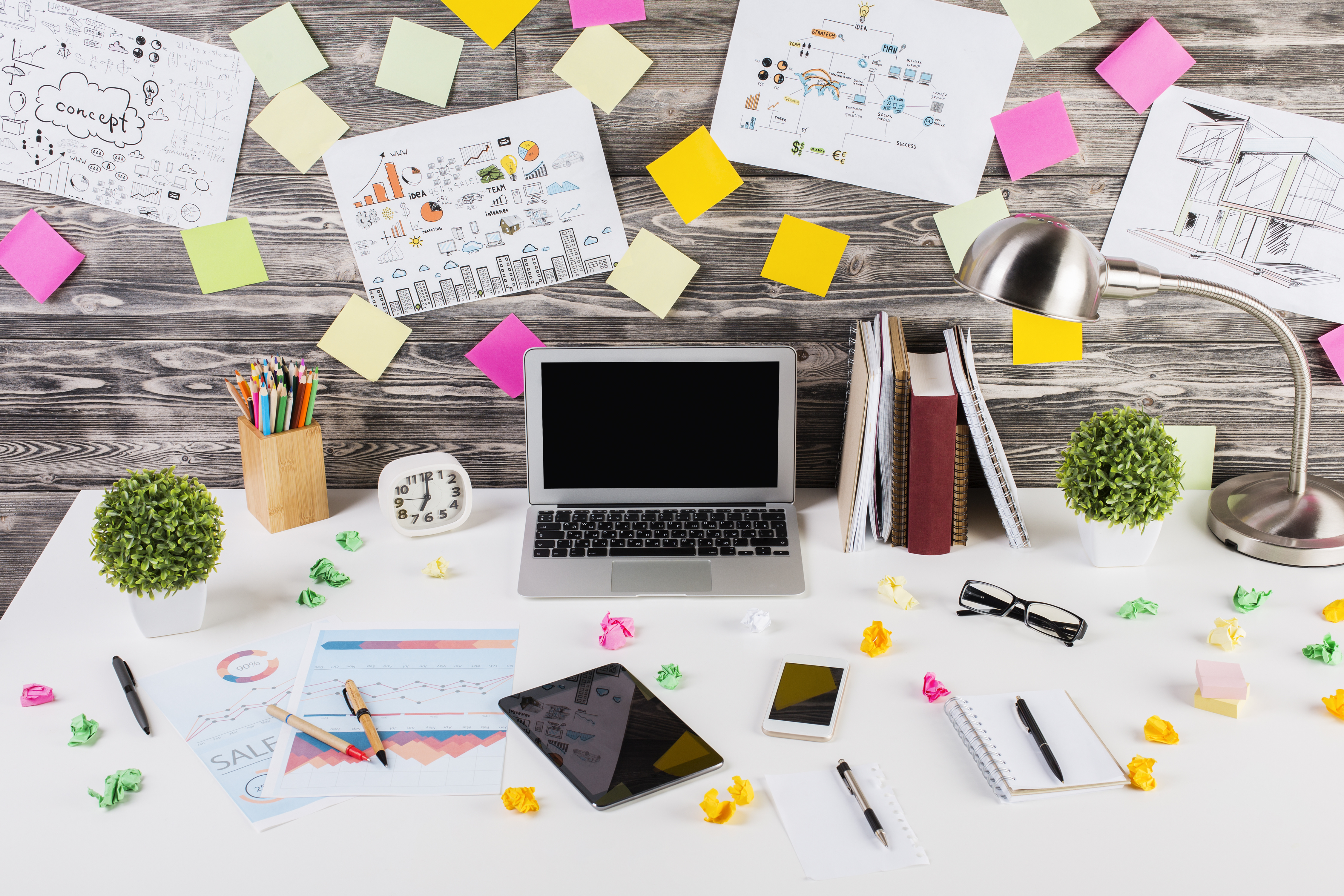 Closeup of modern messy workplace with blank electronic devices, colorful crumpled paper balls, decorative plants, financial reports, creative sketches and other items. Mock up